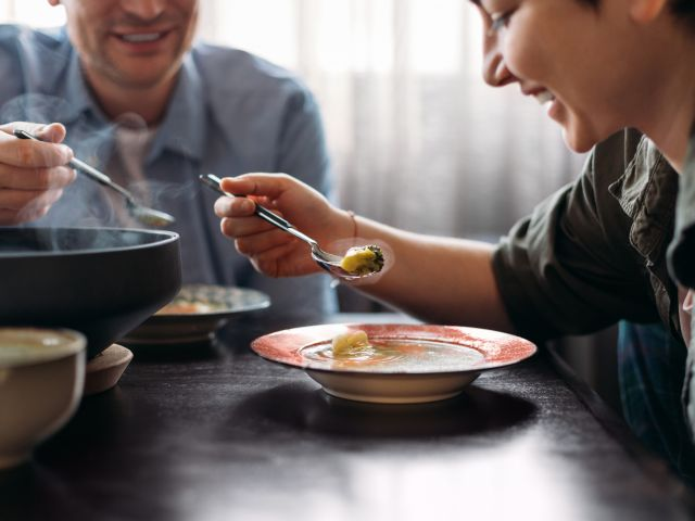 Woman and man eating soup