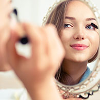 Woman putting on makeup, click to read more